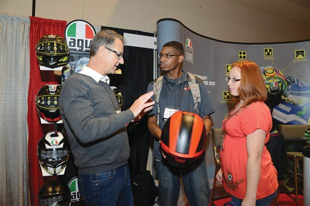 AGV's Mark McPerry shows off the brand's lineup to Curtis Sartor and Nicole Nehlsen from BBK Motorsport in Elgin, Illinois.
