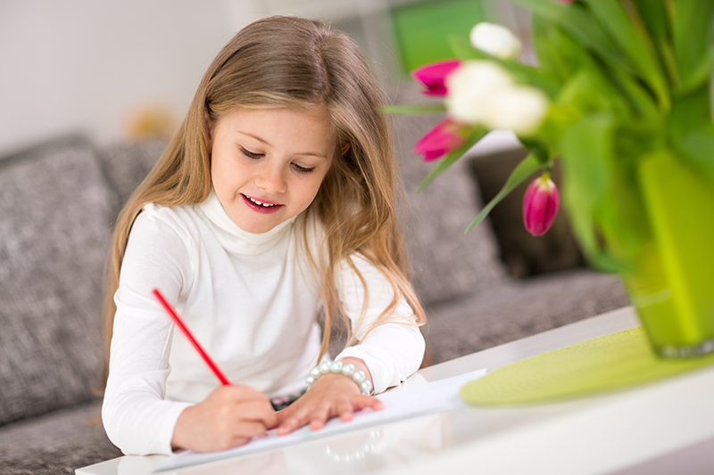 Beautiful happy little girl writing at home