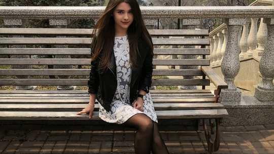 Юная красотка шатенка в платье на скамейке