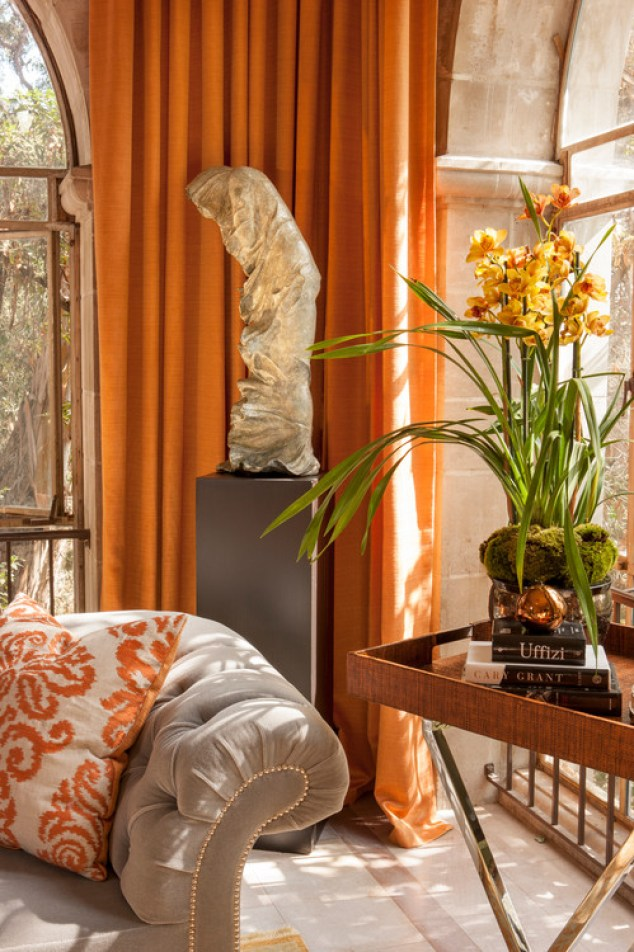 Russet orange drapes hang on either side of large arched windows in a Tudor revival living room. There's grey stonework with elaborate details framing the windows.