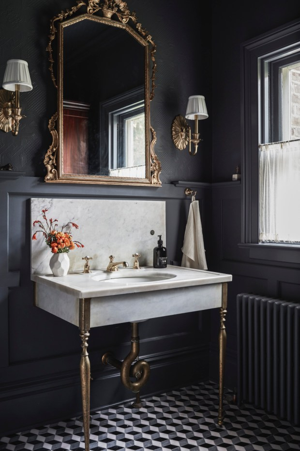 A Glamorous, Dark Bathroom With Elaborate Brass Accents
