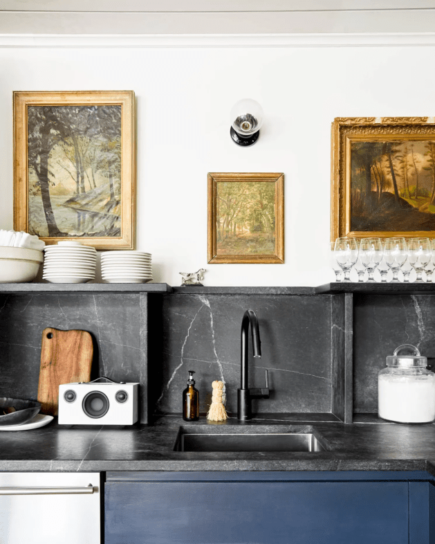 A Moody Kitchen With Framed Vintage Art and Black Marble