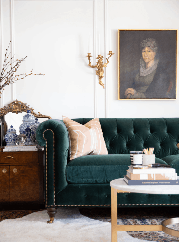 A glamorous, chic, and sophisticated living room uses vintage accent pieces, with the vintage portrait hanging above the sofa being the most prominent.