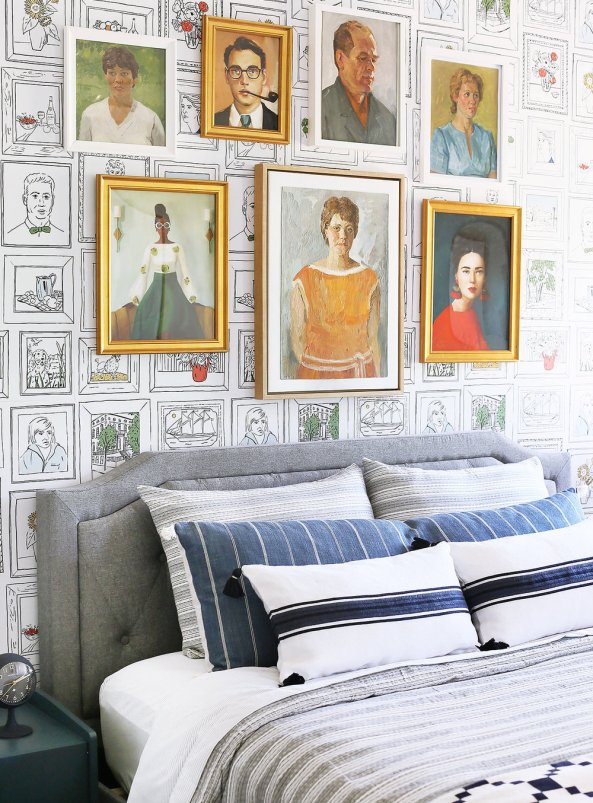 In a whimsical bedroom, a gallery wall of vintage portraits are used in lieu of a headboard. They're placed against an eclectic, collage style wallpaper.