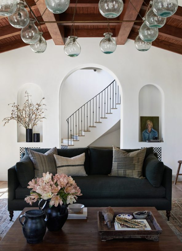 In a remodeled Spanish Colonial Revival living room, there's a vintage portrait in a niche style wall alcove.