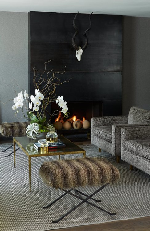An eclectic, industrial-meets- Hollywood Regency living room design with modern steel fireplace, plus glamorous vintage accents like horns, fur, club chairs, and a mirrored brass coffee table