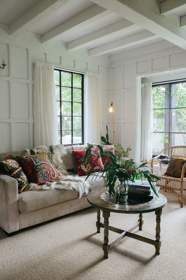 Cozy, boho living room with vintage textiles layered between a medium sheepskin pelt: get the look on a budget