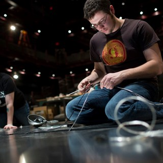 Aaron Bowersox runs electrical wires through boards below a stairway-like art exhibit piece as he and fellow graduate students work to get the piece mocked up at the Wells-Metz Theatre on Thursday, Jan. 8, 2015. The piece will be part of the 2015 Prague Quadrennial of Performance Design and Space in June.