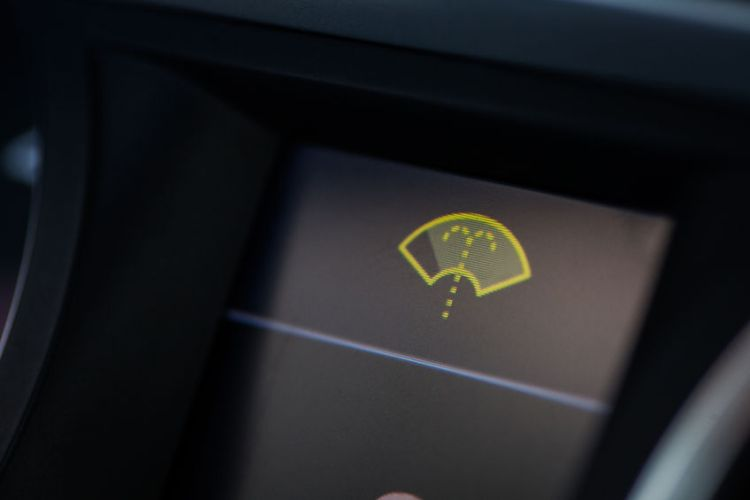 59200870 - close-up shot of a car's dashboard, with the wind screen washer icon lit.