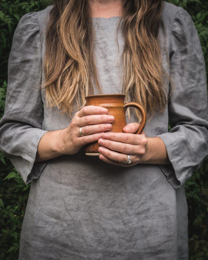 woman holding a brown coffee mug full of homemade bone broth