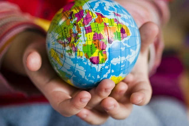 Worldschooling ~ Child's hand holding a globe