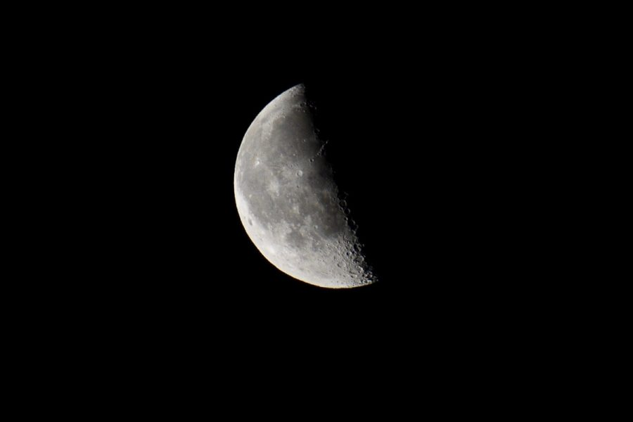 A quarter moon against the dark night sky.