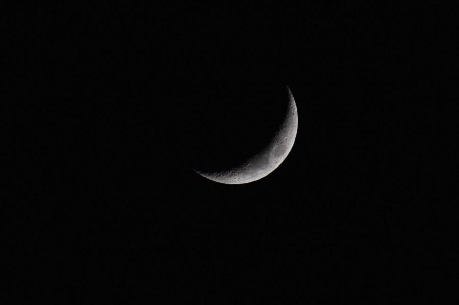 A slight crescent moon shines against a dark black night sky.