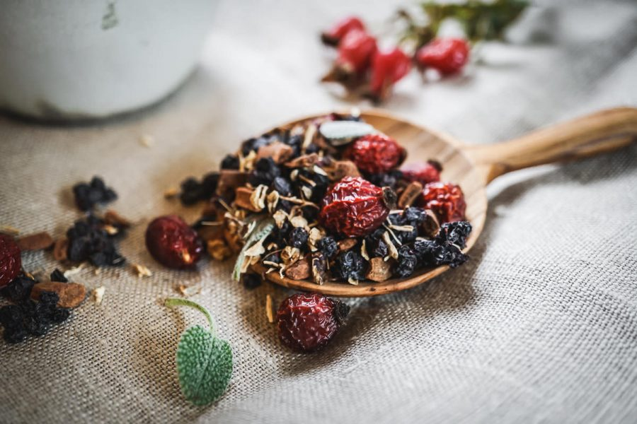 loose leaf tea with rose hips rest in a wooden spoon