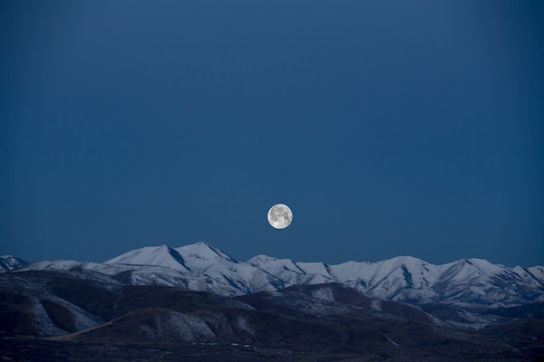 Full Moon Rises over snowy mountains
