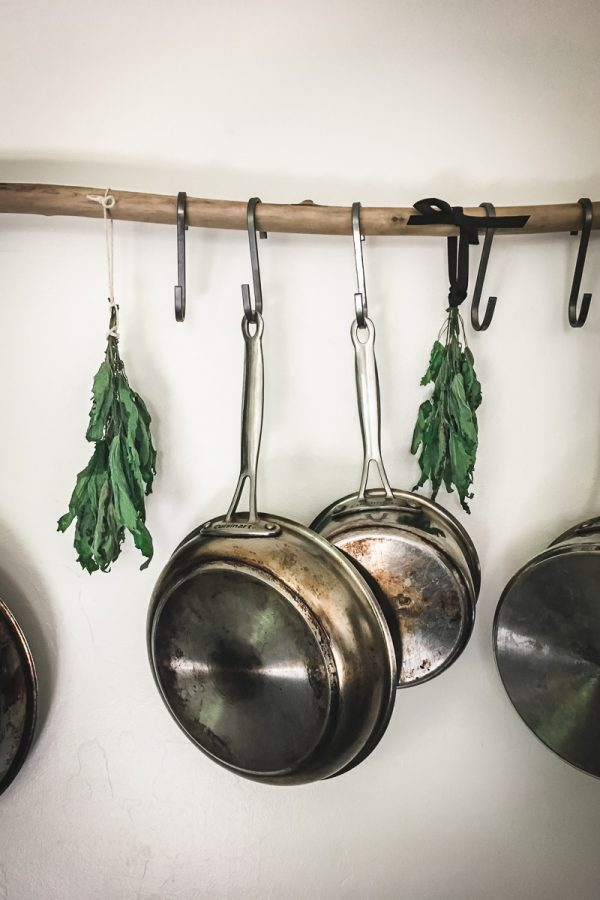 Metal pots and pans and bundles of herbs hang from a stick on a kitchen wall.