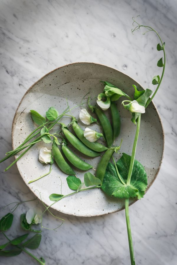 Snap peas and pea flowers in a bowl on marble counter.