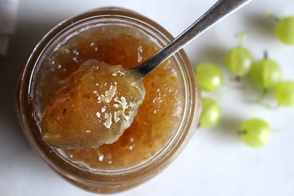 A jar of gooseberry jam, top view with a spoon holding a bit of jam to show the firm set achieved even without pectin.