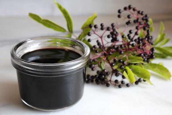 Jar of homemade elderberry syrup with raw honey