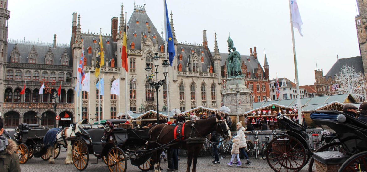 Horse drawn carriages in front of the Christmas Market in stunning Markt Square: Brugges, Belgium in winter.