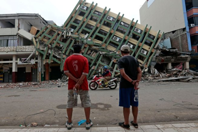 two-men-look-at-a-destroyed-building