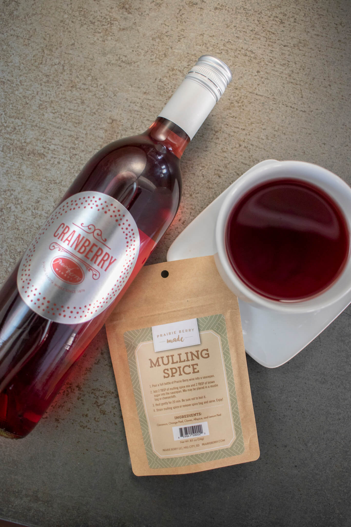 A bottle of Cranberry wine, Prairie Berry Made Mulling Spice, and a mug full of mulled wine
