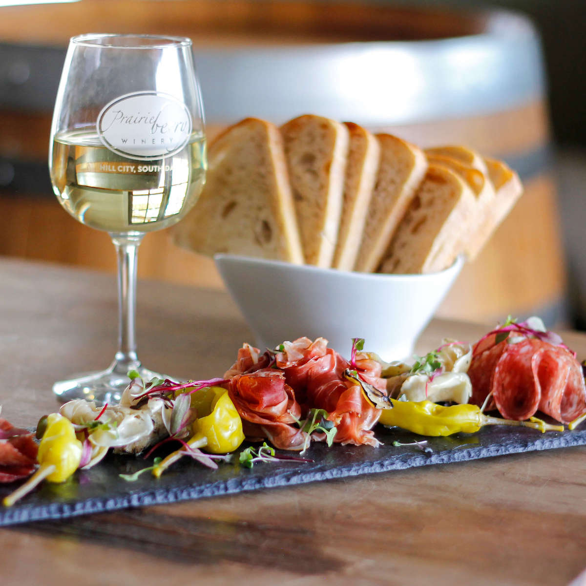Antipasto Platter, a glass of white wine, and sliced bread