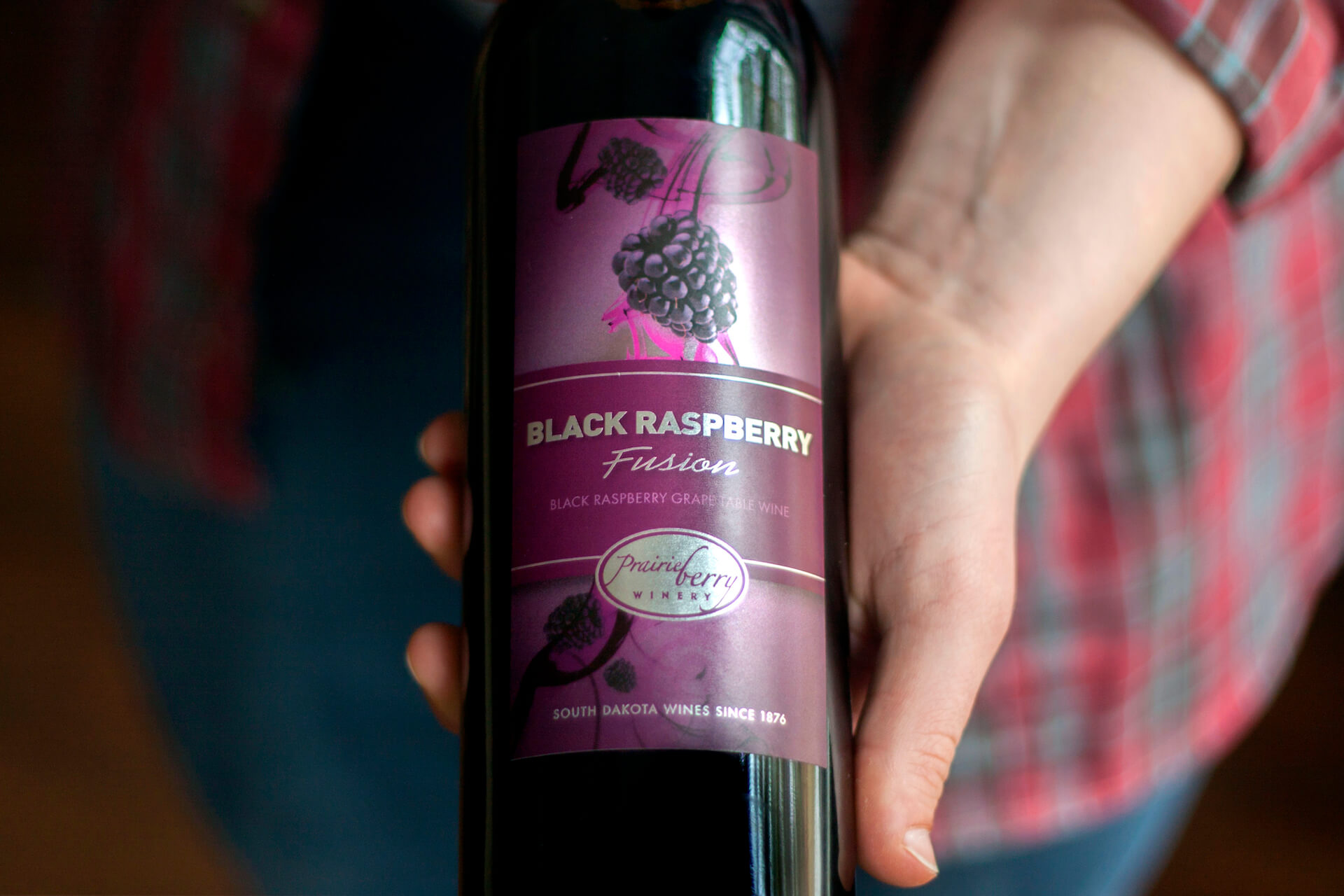 Hand holding a bottle of Prairie Berry Winery's Black Raspberry Fusion