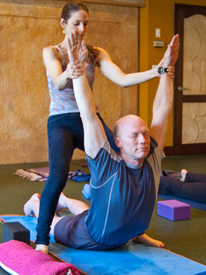 Photo: a yogini assists a yogin arch back