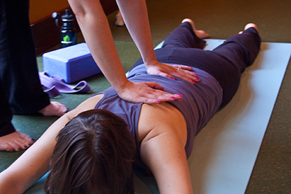 Photo: hands are placed on the back of a supline yogini