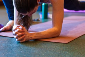 Photo: a woman with her forearms placed on the mat, legs in a deep lunge