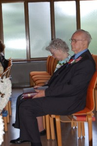 Photo: elderly man and woman seated in a church