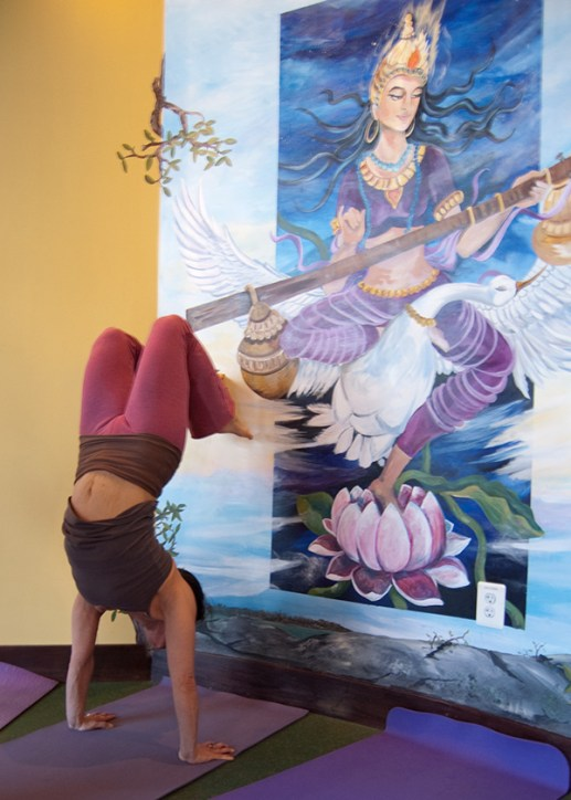 Photo: a yogini does a handstand in front of a painting of Hindu goddess