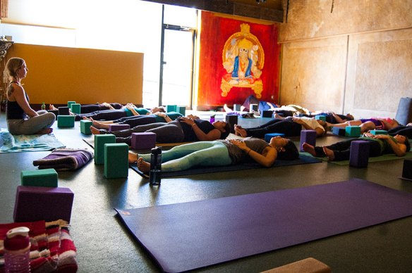Photo: yoga teacher has students lying on their mats