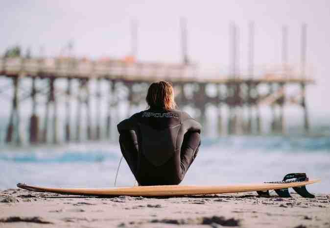 surfista sentado na areia da praia