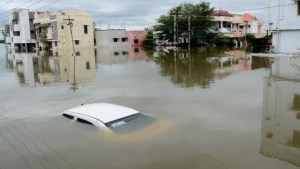 A car is submerged amidst water-logged houses in a rain-hit area of Chennai on November 17, 2015. India has deployed the army and air force to rescue flood-hit residents in the southern state of Tamil Nadu, where at least 71 people have died in around a week of torrential rains. AFP PHOTO / AFP / STR