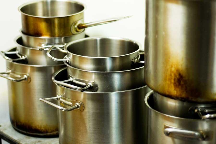 Panelas de metal dispostas uma sobre a outra e dentro