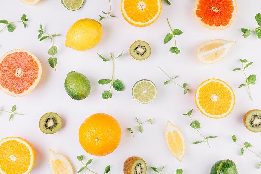 Fundo branco com frutas cítricas e ervas distribuídas em padrão
