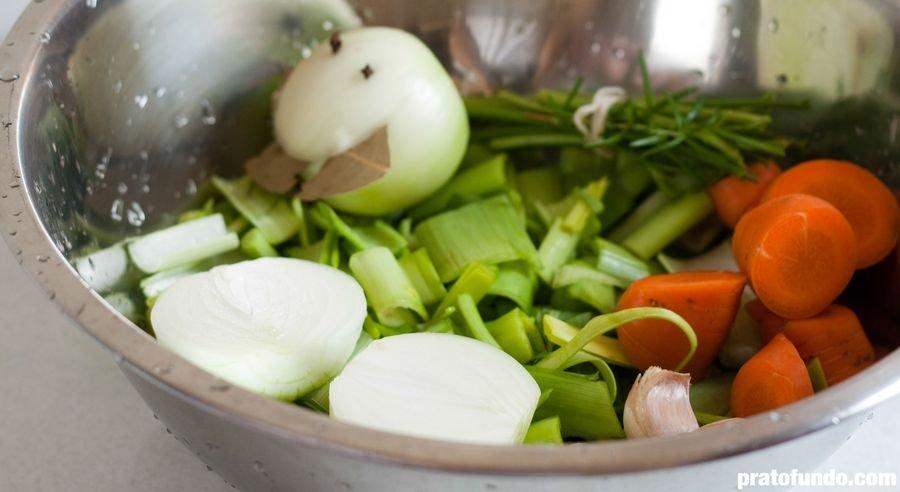Mix de vegetais cortados dentro de uma tigela de metal para fazer caldo de legumes visto de lado