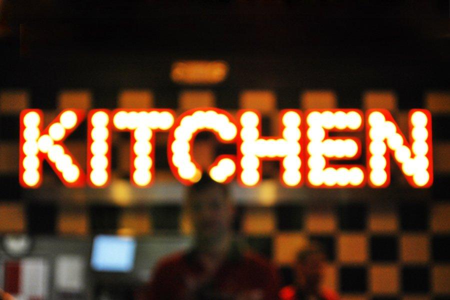 Foto de um letreiro iluminado escrito Kitchen, cozinha em inglês.