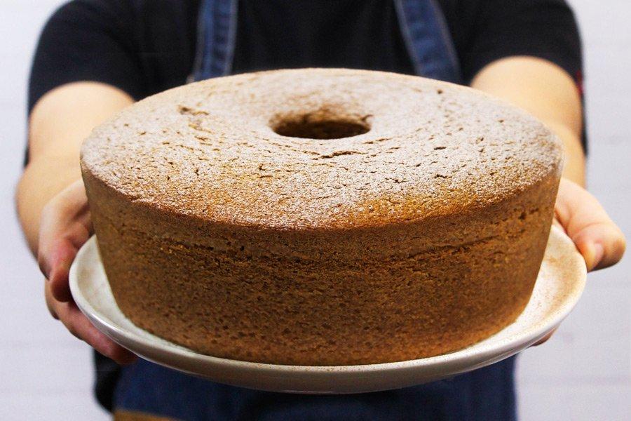 pessoa segurando um prato com bolo dentro
