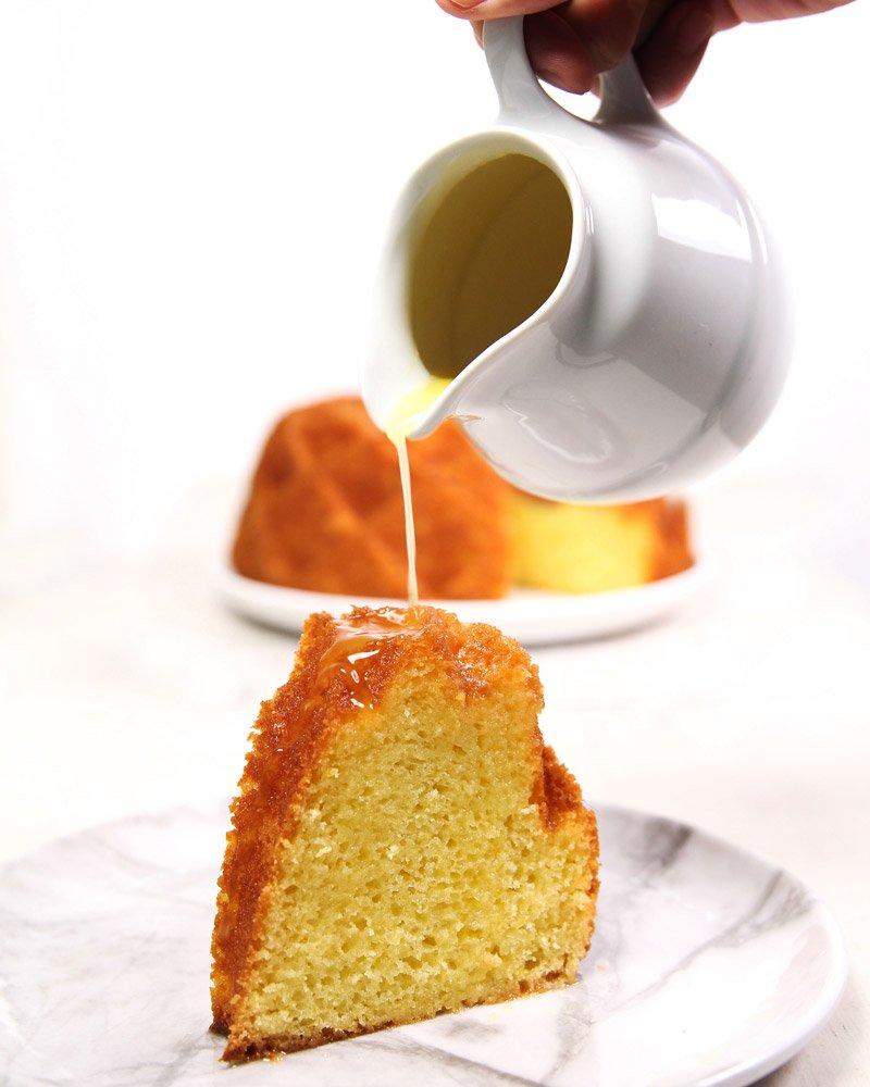 Fatia de bolo de laranja sendo regado com calda de laranja