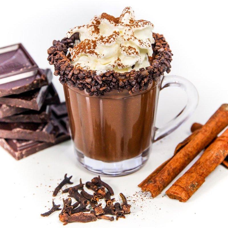 Chocolate quente com chantilly dentro de uma xícara cercada por chocolate, cravos e canela