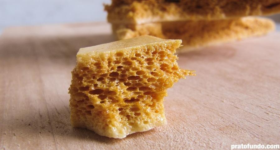 Pedaço de Honeycomb Candy em detalhe sobre tábua de madeira