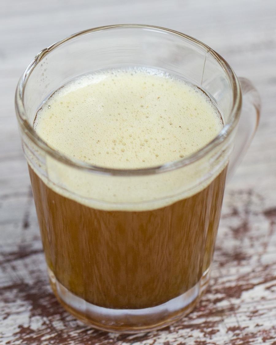 Xícara de vidro transparente com a manteiga queimada dentro, coloração dourada  em close e com espuma na superfície