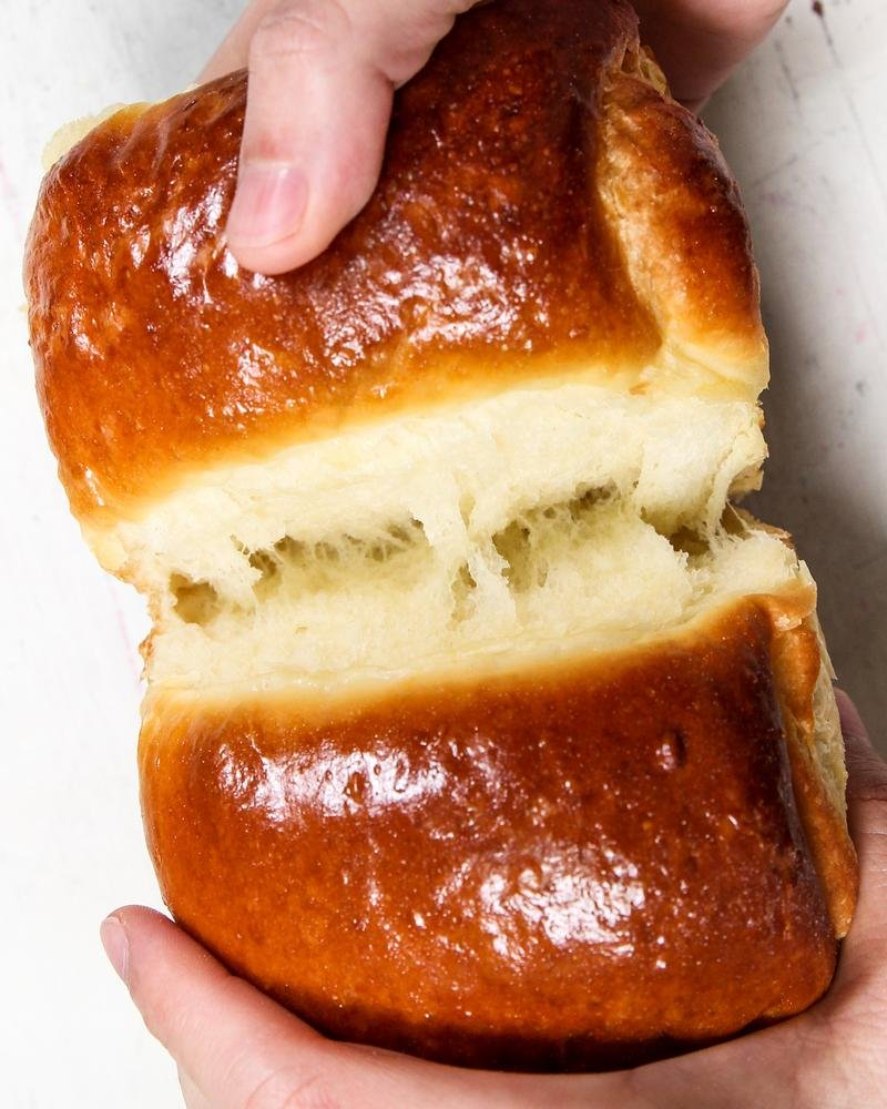 Separando um gomo de pão de leite mostrando o rasgo da massa