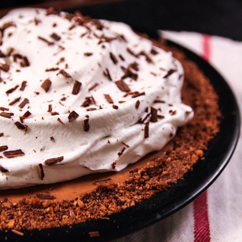 Torta Mousse de Chocolate inteira com cobertura de chantilly e raspas de chocolate em cima.