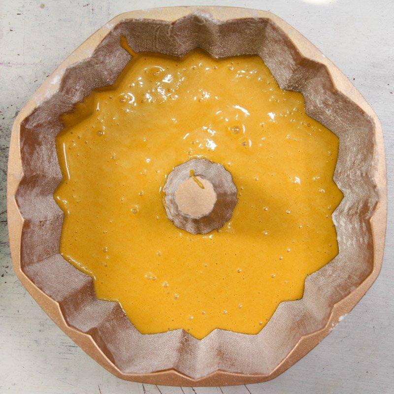Massa crua de bolo de cenoura feito com mistura de bolo da Fleischmann dentro de uma forma de furo no meio sobre uma mesa.