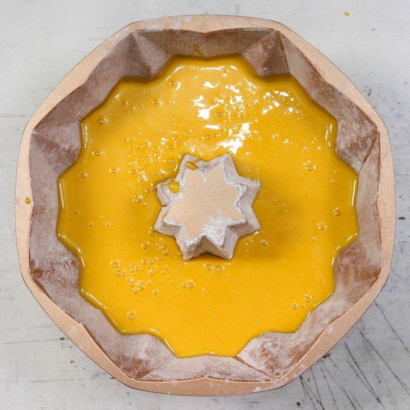 Massa crua de bolo de cenoura feito com mistura de bolo da dona benta dentro de uma forma de furo no meio sobre uma mesa.