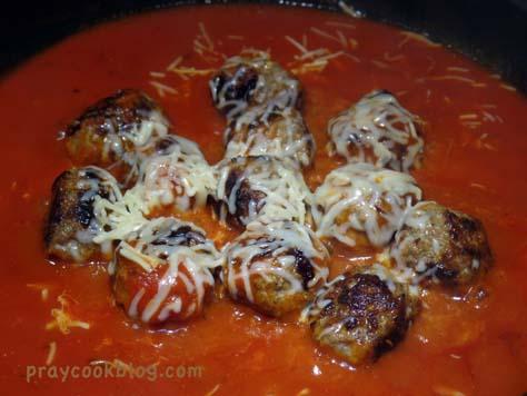 Simmering meatballs in sauce.